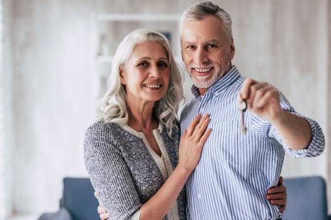 Elderly couple holding key