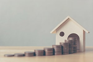 coins in front of a model house | Mortgage Refinance