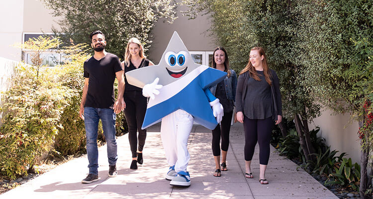 People and mascot walking outside | Company culture