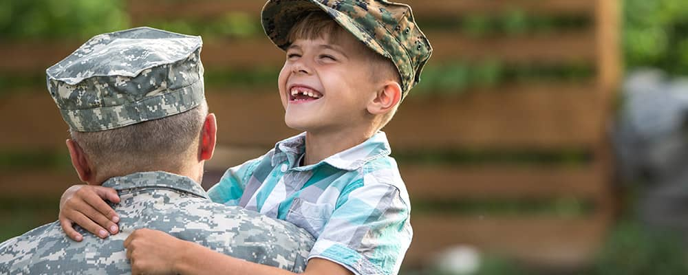 military father holding laughing son