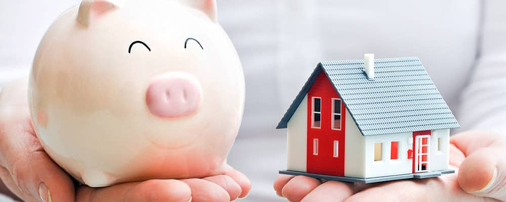 woman holding a piggy bank and house model