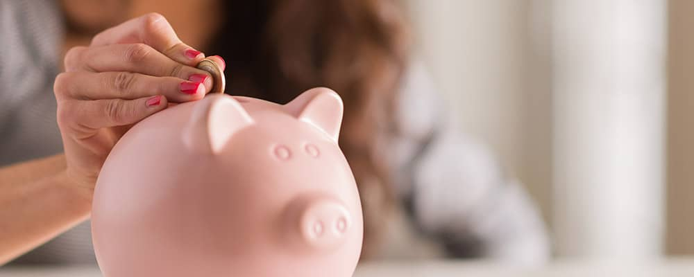 woman putting a coin into a piggy bank