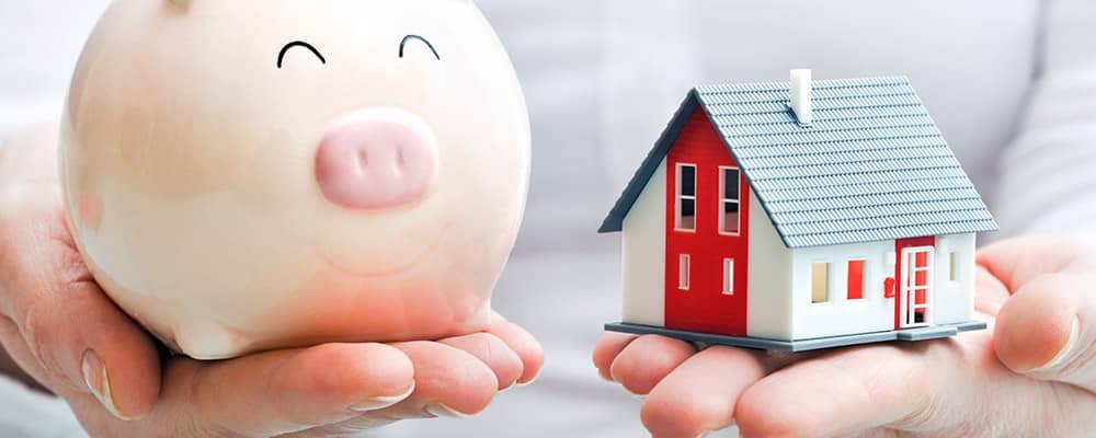 woman holding a piggy bank and house model in her hands