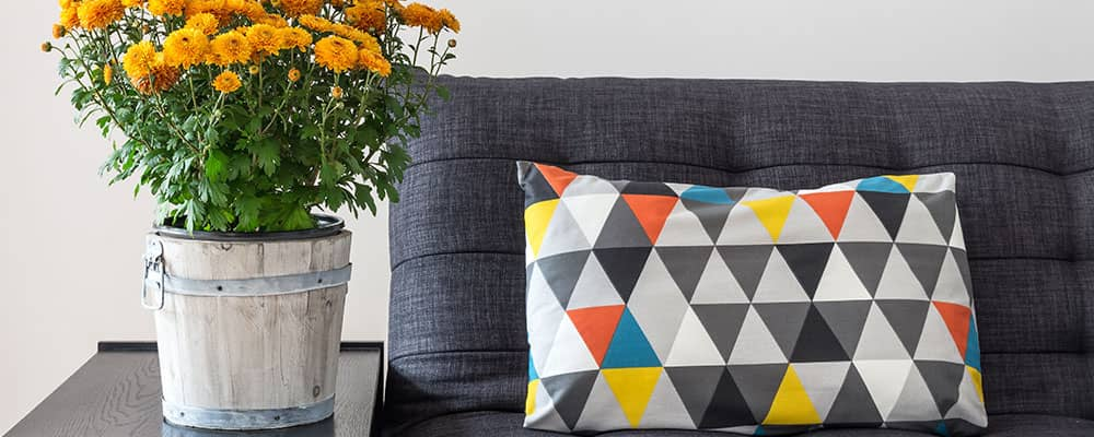 couch with a colorful triangular patterned throw pillow next to a side table with a bucket of flowers on top