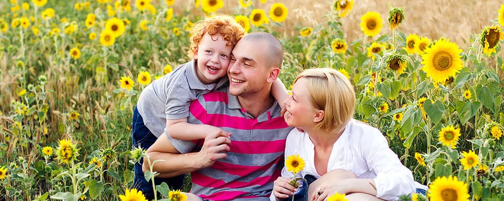 family sitting a field of sunflowers