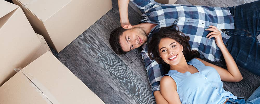 couple lying on hardwood floor surrounded by moving boxes