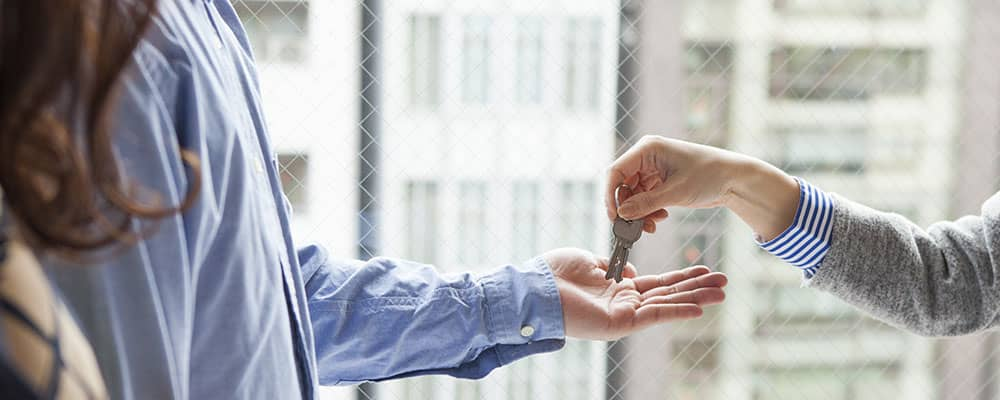 real estate agent handing keys to home buyers
